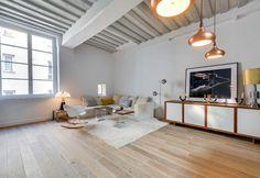 Le travi a vista – segno della storicità dell'edificio – sono state mantenute e dipinte di bianco in questo appartamento parigino ripensato nel 2014 dalla progettista Tatiana Nicol, la quale ha disegnato la maggior parte degli arredi