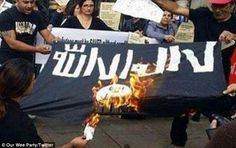 Burning hatred: Protesters in London set fire to an Islamic State flag in a new craze that has adapted the Ice Bucket Challenge to vent their disgust at the terror group's brutality