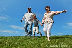 Boy and grandparents running on summer lawn