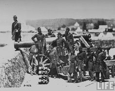 Officers of Irish 69th NY Militia surrounding 8-inch seacoast howitzer as their commander Col. Michael Corcoran (far, L) stands to side, during early days of Civil War, at Fort Corcoran.  Location: Arlington, VA, US  Date taken: 1860