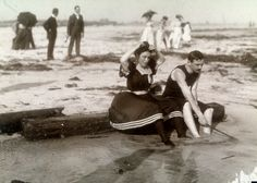 A couple sits on a log at the water's edge in Far Rockaway in New York City's Queens borough, 1897. Men and women in day clothes take a stroll in the background.