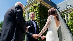 Bride and groom are holding each others hand while sharing their vows