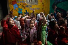 Oct. 19, 2012. Pakistani students, displaced along with their families from Pakistan's tribal areas due to fighting between militants and the army, chant a song with their teacher, not pictured, during their daily school in a poor neighborhood on the outskirts of Islamabad.
