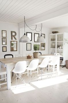 White dining room with rustic earthy accents. Love the combination of a modern chair with rustic table: