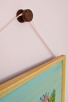Young House Love's Round Wood Hook used as a decorative picture hanger. But looks can be deceiving! Check out the clever decorating idea from John and Sherry of Young House Love.