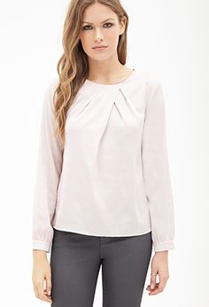 Simple blouse with diagonal pleats at the neckline for visual interest. The model paired this outfit with black cigarette pants and warm grey pumps. In another picture she wore a muted pink coat over it.
