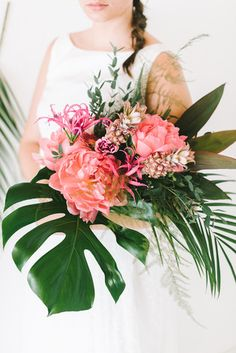 Brautkleid Zweiteiler mit Bluse und Rock aus gepunktetem Tüll und modernem Brautstrauß mit Palmzweigen und Philodendron Blättern…