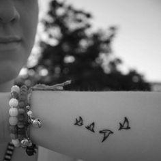 Pequeño tatuaje en el antebrazo de cuatro golondrinas volando.