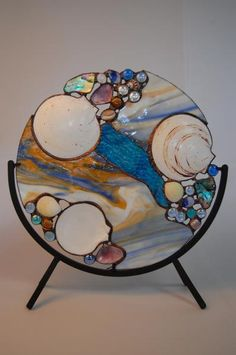 bake seashells, maybe some glass agates and then the plastic beads that melt, into an aluminum pie plate like the wind chimes?