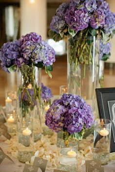 Pretty purple flower centerpieces combined with candles and flower petals