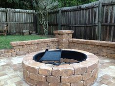 Outdoor Retreat Area with Fire Pit, Small Bench Wall, Column with Lighting by StoneCraft Pavers in Orlando, FL