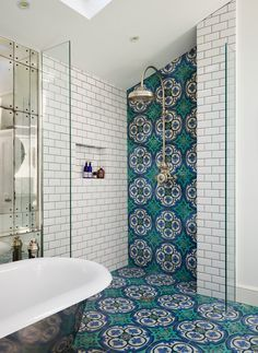 Stunning Victorian bathroom with white subway tile, beautiful Moroccan tiles along the floor and shower, stainless steel oversized shower head and a metallic freestanding tub.