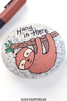 """Learn how to paint a sloth with paint pens. This sloth painted rock is perfect for beginners. Use this rock painting idea to hide around your town, give as a gift, or decorate your home. Add the phrase """"Hang In There"""" to create a cute kindness rock. #sloth #paintpens #paintedrocks #rockpainting101 Rock Painting Supplies, Kindness Rocks, Painting Videos, Paint Pens, Learn To Paint, Animal Paintings, Cartoon Styles, Sloth, Painted Rocks"""
