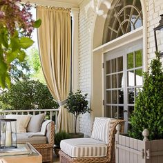 Love the curtains to give privacy and the simplicity of the bushes in pots