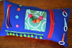 Activity pillow with soft textures and bright colors provides sensory stimulation for those with Alzheimer's Disease or other cognitive impa...