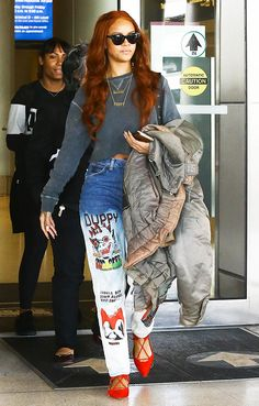 Rihanna wears a gray cropped sweatshirt, gold jewelry, printed jeans, and red suede Aquazzura flats