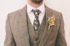 The antique style of his suit and florals is a perfect combination