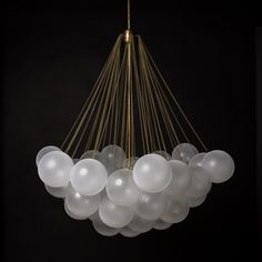 Cloud | Apparatus. Glass orbs are frosted by hand to create an irregular texture reminiscent of 19th century glass frosting techniques. Three central light sources emit a soft glow that is refracted through the surrounding cluster of orbs.