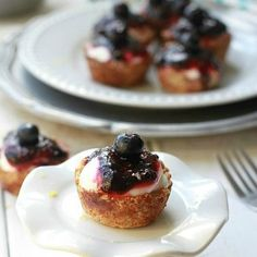 Mini Blueberry Lemon Almond Cheesecakes - These easy gluten free mini blueberry cheesecakes are made with an almond flour crust, lightened up cheesecake filling and topped with a homemade blueberry sauce.