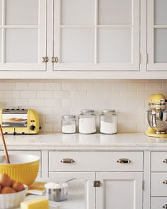 White kitchen with yellow retro accessories