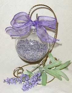 "clear glass Christmas ball ornaments. Remove the hanger and fill the glass ball ornaments about half full with dried lavender. Reattach the hanger. Slip a length of 1"" wide purple organza ribbon through the hanging wire and tie a bow. These ornaments make nice Christmas gifts."
