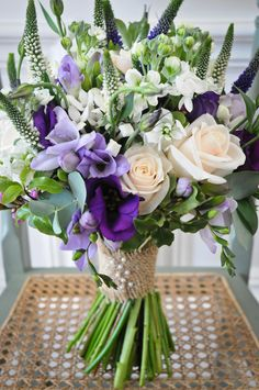 Lilac and purple freesias with white bouvardia and cream roses for a more natural handtied bouquet , tied with a hessian ribbon