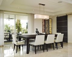 The transition from the dining area to the patio is made seamless with floor-to-ceiling sliding glass doors that let light in and provide a view of the surrounding palm trees and other vegetation.