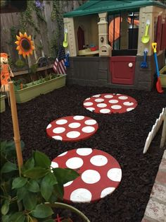 Kids backyard play garden. Up-cycled old stepping stones to look like mushrooms. Used exterior paint and an exterior waterproof sealant. Rubber mulch from Home Depot.