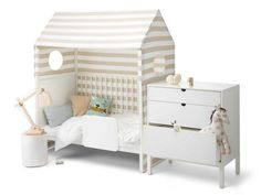When your child outgrows the Stokke Home crib, drop the mattress and remove a side panel to turn it into a child-size bed. Shown here with a beige-striped crib tent. via HOUSTON CHRONICLE