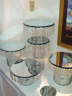 looks like they used dollar store vases and attached mirrors to the top then the jewels. I would spray paint cheap candlesticks silver and place in between the mirrors to create a cupcake stand - Crafts Are Fun Dollar Store Crafts, Dollar Stores, Thrift Stores, Diy Centerpieces, Centrepieces, Dollar Tree Centerpieces, Bling Centerpiece, Candy Table, Candy Buffet