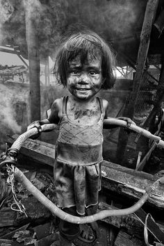 Thomas Tham. It is amazing to me, that this child can smile with the turmoil around her. She picks up a wired conduit to be used as her new found toy. She smiles. She plays. She is a child. Not knowing the world around her disintegrates. Or maybe she does know.
