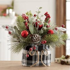 "Add a touch of farmhouse plaid this season! Natural twigs and pinecones bundled with frosted red ornaments, faux glittered leaves, berries and greenery. Fabric bag base is tied with a jute rope. 11"" w x 12"" h x 9"" d."