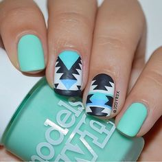 Cute and abstract designs on blue green nail polish. This nail art design uses blue green nail polish under black and white shapes and line details that look fun and adorable to look at.