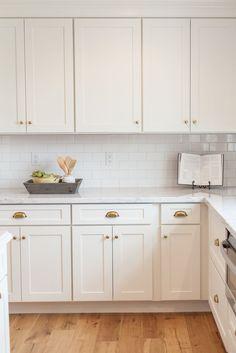 A stainless steel oven range sits against white herringbone ...