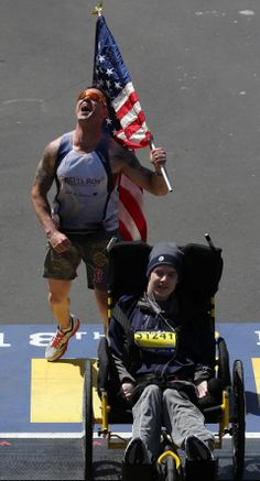 Lucas Carr, running with theTravis Roy Foundation, carried an American flag as he pushed Matt Brown across the finish line of the Boston Marathon. 04/21/14 David L. Ryan/Globe Staff