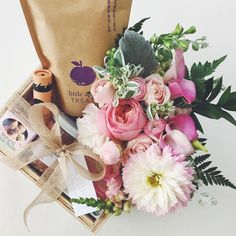Gift basket for new mama. Flowers, healthy snacks, natural baby care, bath salts and candle. Tied up with pretty ribbon in a basket. DIY