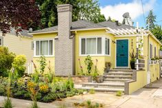 AFTER To make the home pop, designer John Gidding chooses sunny yellow for the siding and cheery turquoise for the front door. The winding stairs are straightened and widened to draw more attention to the front entry which is shaded by an arbor, planted with fragrant honeysuckle. The homeowners aren't big fans of mowing the grass so John eliminated the lawn in favor of a wide stone path flanked by low-maintenance plants.less...