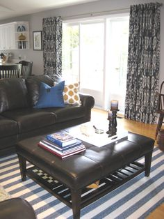 Colour makes a big difference when you have neutral coloured furniture. In the background, you will see a pair of stunning ikat drapes which frame their huge four panelled patio doors. If you've got it you might as well flaunt it! Open Shelving, Shelves, Round Ottoman, Sofa, Couch, L Shape, Colorful Furniture, Patio Doors, Glass Table