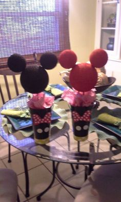 Mickey or minnie mouse birthday party center pieces. Styrofoam, paint, popcicle sticks, cups, ribbom, buttons, tissue paper.