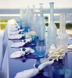 Seaside: milky, sandblasted and tinted glass is a key decorative element, with bottles and hurricane lamps taking the place of traditional centerpieces