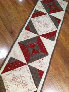 Table runner. Lovely use of machine embroidered quilt blocks. Autumnal colours and redwork. Perfect