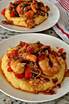 These delectable Shrimp and Grits are cooked with Cajun seasoning, red pepper, green onions, crisp bacon and garlic over a bed of creamy cheddar grits.