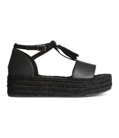 Platform sandals with braided jute trim around soles. Decorative tassels at front and adjustable ankle strap with metal buckle. Imitation suede insoles and rubber soles. Platform height 1 3/4 in.