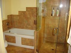 A concrete wall and floor overlay was hand applied right over this old tile shower to give it a completely grout-free decorative surface. The overlay, which is stained to look like travertine, was also applied to the tub surround and bathroom floor to tie the look together.