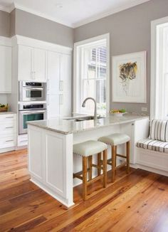 Built in oven. White cabinets. Like the wall and cabinet contrast. Wood kitchen flooring, plus sink island.