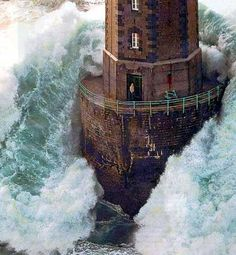 waves crashing over lighthouse