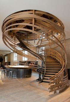 A dramatic spiraling staircase comprised of multiple oak strips is the centerpiece of the bar area in the restaurant Brasserie des Haras located in Strasbourg, France. [1200 × 1733] : RoomPorn
