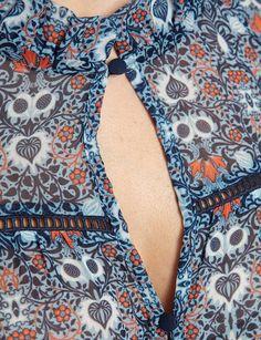 Top coupe fluide<br/>Manches 3/4 volantées<br/>Col montant froncé<br/>Découpe et boutons au décolleté<br/>Épaules dénudées<br/>Liserés ajourés en haut de la pièce devant et au dos<br/>Imprimé à fleurs multicolores<br/>Tissu légèrement transparentCRLF Nom : 161-FOWA.N