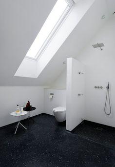 Badeværelset er med støbt terrazzogulv og Vola-armatur designet af Arne Jacobsen. Små borde til ham og hende er fra Hay.