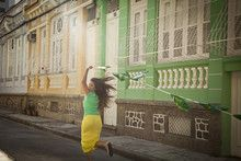 Young woman celebrating with Brazilian flags in the street, Rio de Janeiro…